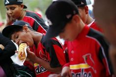"A boy eats a hot dog after a baseball practice at the ""23 de Enero"" neighborhood in Caracas March 1, 2011.  REUTERS/Jorge Silva"