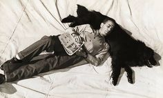 Humphrey Bogart taking a nap and using his Newfoundland dog, Cappy, as a pillow.