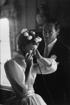 Audrey atendiendo al teléfono, detrás su marido,Mel Ferrer. El día de su boda.