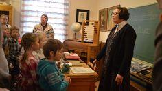 opettaja ja lapset laulavat vanhanajan koulussa