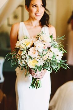 large peachy pink bouquet .| oversized wedding bouquet with lots of leafy greenery