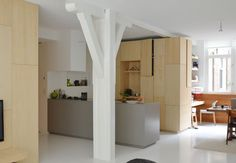 a seamless kitchen packed with birch wood cabinets designed to look like furniture