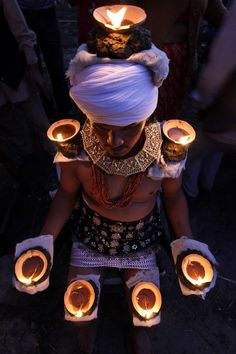 A Nepalese Hindu devotee places burning oil lamps on his body as part of rituals to celebrate the tenth and final day of Dashain festival at Bhaktapur, on the outskirts of Katmandu. (AP)