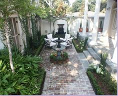 New Orleans-style courtyard: stone, brick, rod iron, white cushions, white vertical fence, faux louvered doors set in fence, tiered fountain surrounded by small potted plants as a focal point, faux fireplace at end of path against fence.