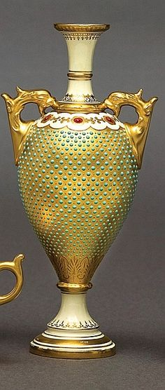 Brian W you will love this one ! A W   A Coalport jewelled vase, circa 1910, cream ground with slender neck and footed tapering body with extensive turquoise jewelling and gilding, two dolphin loop handles, green printed mark