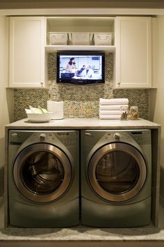 Jazz up a laundry room with a little back splash, white cupboards, and a place for a TV...I need a TV