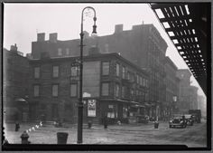 [Vacant wood frame tenement with storefronts; Bishop's crook lamp: 9th Ave. - W. 17th St., Manhattan] (1935-1936). NYPL Digital Gallery.