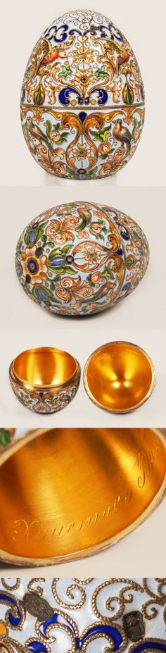 "A Russian silver gilt and shaded cloisonne enamel egg, Feodor Ruckert, Moscow, Circa 1896-1908. This is generously ornamented with birds in shaded enamels set amongst scrolling floral and foliate enamel against a pale blue ground, the interior gilded and engraved in Cyrillic with the Easter greeting""Christ has Risen"""