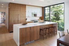 cuisine avec des armoires en bois et façades blanches, îlot fonctionnel et tabourets de bar en bois