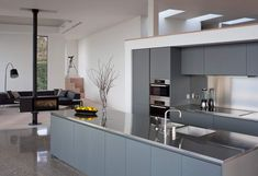 12 Examples Of Sophisticated Gray Kitchen Cabinets // The darker gray of these kitchen cabinets works with the other dark elements in the living room just off to the side, and the stainless steel countertops help to reflect light, making the kitchen appear brighter.