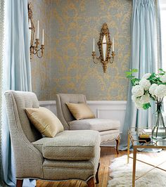 sitting room with blue gray gold wallpaper chairs with nail head trim blue curtains wall sconce elegant decor ideas thibaut