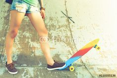 Close-up skateboarder girl with skateboard outdoor at skatepark