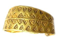 Early Medieval Viking gold finger ring, 9th-10th century. The ring is substantially gold and consists of a broad, punch-decorated band tapering sharply at each end to wire terminals which were originally twisted together.