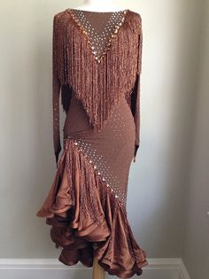 Sultry, sexy and sophisticated. Cocoa dress is made with European fabrics and metallic bronze fringe. Lots of movement! Covered with Swarovski stones. Bra cups and body suit. Fits sizes 2-6 and best for heights above 5'3""