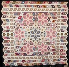 This quilt was named Honeycomb (Rayon de miel) by its maker, Liliane Verger of Royan, France. It was inspired by an English quilt; quilts such as these were much appreciated in England in the Victorian age (circa 1840). The hexagons were all made using the English paper method.