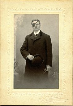 Man with Eyepatch and Overcoat Holding a Bowler by depthandtime, via Flickr