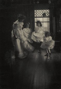 In a scene like something from a charming movie, we see a woman and three young girls (from 1905) dancing about merrily on a wooden floor.