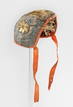 Infant's christening bonnet, Norway, 1725-1775, earlier embroidery. Silk brocade with floral metallic thread embroidery, edged with an orange silk ribbon, block printed linen lining.