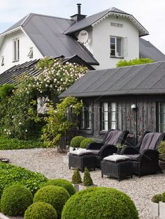 A perfect English retreat features lots of well manicured boxwoods and comfortable lounge chairs.