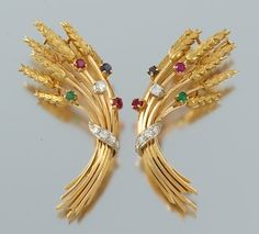 A pair of gold, diamond, ruby, sapphire and emerald brooches in the form of wheat sheaves, symbols of harvest/attainment. (aspireauctions.com)