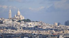 The Sacre Coeur glowing white and bright in the sunlight viewed from a distance on top of the D'Orsay or the Pompidou.