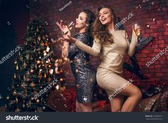 Portrait of two smiling girl with tinsel confetti in hands and wineglasses with champagne. New year's feeling. Merry christmas