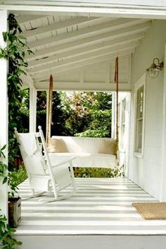 A lovely southern back porch with a wicker rocking chair and swing