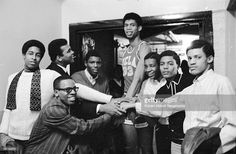Boxing great Muhammad Ali, back row, second from left, looks up and smiles at UCLA basketball player Kareem Abdul Jabbar, back row, center, then known as Lew Alcindor, during the UCLA Bruins' trip to play Loyola University, Chicago, IL, 1967. The others are unidentified and may be UCLA students in town to support their team. (Photo by Robert Abbott Sengstacke/Getty Images)