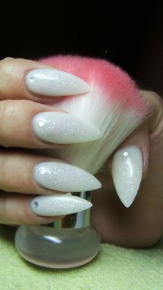 White stiletto nails with glitter and rhinestones