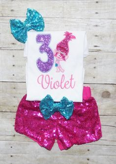 Be sure and Like me on Facebook for special offers and new designs! www.facebook.com/mommamayshop   Trolls birthday outfit!!!  Something new!!  Some much versatility of this kind of outfit!! Embroidered bodysuit/shirt, fabulous hot pink 1 sided sequin shorts, and bow for her hair. Pink and Hot Pink sequin pants are also available!!!! Perfect for bounce house parties, outdoor parties or a comfortable addition the the tutu set!!  Her shirt will be embroidered with her birthday number,...