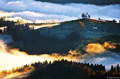 The hills around Škofja Loka and the Church of St. Thomas rising above the morning mist. Slovenia