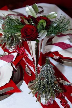Image of 'Christmas table with red decoration, napkins, roses, silver, christmas tree and candles'