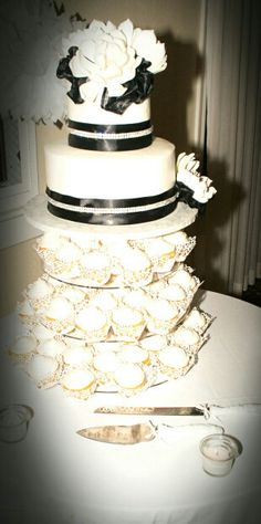 My wedding cake with 50,cupcakes- I actually had the cupcakes made at Shaws and put my own cupcake wraps on. Cake: $200, Cupcakes: $45, Wraps: $15, and Stand: $60. Everything i wanted and saved over $300 by doing things the way i did :)