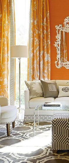 Warm ivory and orange/marmelade tones with greige accents, pattern mix, airy glass/metal coffee table
