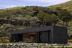A dark rough-sawn timber box in New Zealand, Storm House