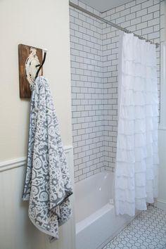 El baño se iluminó aún más con azulejo blanco de metro y lechada de color gris oscuro. Coordinación de ropa de baño y ganchos de pared antiguos ayudan a completar el look.