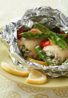 Grilled-Fish Foil Packets — Fancy rolled-up Sole fish fillets with Chive Onion Cream Cheese topped with asparagus and peppers cook up quickly and deliciously wrapped in foil packets with lemons for the grill.