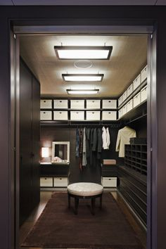 Masculine dressing room; dark wood w/ white pops in ottoman and storage boxes; chrome framed fluorescent lighting; Cleveland Harp