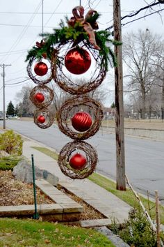 DIY Oversized Outdoor Christmas Decoration / use 3 different size grapevine wreaths w/ large plastic ornaments hung inside each wreath. Top w/ greenery & bow - - - Bookmark Your Local 14 day Weather FREE > www.weathertrends360.com/dashboard No Ads or Apps or Hidden Costs #outdoorchristmasdecor
