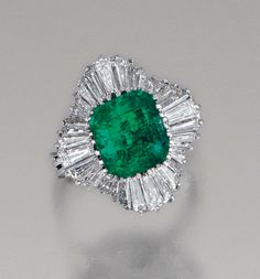 A ring centring on a step-cut emerald within a ballerina surround of tapered baguette diamonds, mounted in white gold