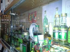 Vitrine présentée par le blog @delachartreuse aux caves Bossetti à Paris : objets de collection pour présenter l'évolution de la #chartreuse Verte au fils du temps...