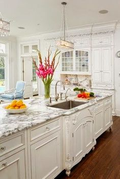 Love the white kitchen, the marble counter tops, but what really drew my eye were the the hit Punic gladiolus