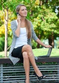 Beautiful young business woman sitting on a park bench and talking on a cell phone