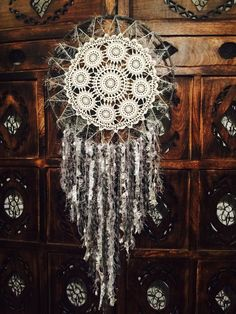 Handmade crochet dream Catcher!  this one has a really unique dolie with a mix of white and grey tassles. Measurements are 42 cm across.  Long tassles, a metre in length from top to bottom of lace tassle,
