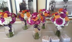 Bright orange and purple flowers on a background of white were this bride's vision for her outdoor golf club wedding. Roses, dahlias and dendrobium orchids mixed with hydrangea and stock with purple ribbon wraps from Seasonal Celebrations.