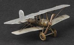 WWI RFC - Trench Art Bullet Biplane. An original artificer-made model of an Sopwith-style biplane, c.1917, of .303 bullet fuselage with brass nose-cowl and propeller, and open cockpit and wheeled undercarriage detail, engine-turned aluminium wings, tail-pane and rudder with copper bracing-wires etc., wingspan 5.5ins