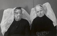 Vrouwen uit Wissenkerke in Noord-Bevelandse dracht. 1956 Links een vrouw met een 'lange muts', met brede kantstrook en 'steenbellen' aan het oorijzer. Rechts een vrouw met 'lange muts', met smallere kantstrook. Dit is de zondagse muts van de minder gesitueerden en de opknapmuts van de beter gesitueerden. Aan de krullen van het oorijzer draagt ze 'halve steenbellen'. #NoordBeveland #Zeeland
