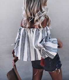 Gorgeous Summer Off Shoulder Blue And White Linen Striped Blouse With Dark Red Tassels Around The Wrist And Trumped Sleeves. styled With A Distressed Denim Shorts And A Small Handbag Perfect For The Blonde Beach Waves In Town/City.