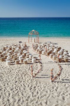 An intimate ceremony on the beach is complete with a fabulous serpentine wedding aisle and modern pods.