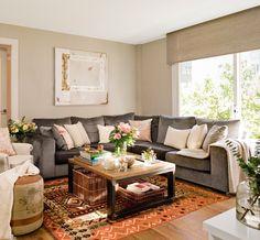 Salón con sofá en L de terciopelo gris. En el salón Sofá, mesa de centro, bandeja y cestas de Cado.